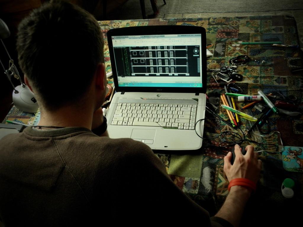 Zdjęcie: Chłopak odwrócony do czytelnika tyłem pracuje na laptopie w programie AutoCad. Na stole leżą kolorowe długopisy