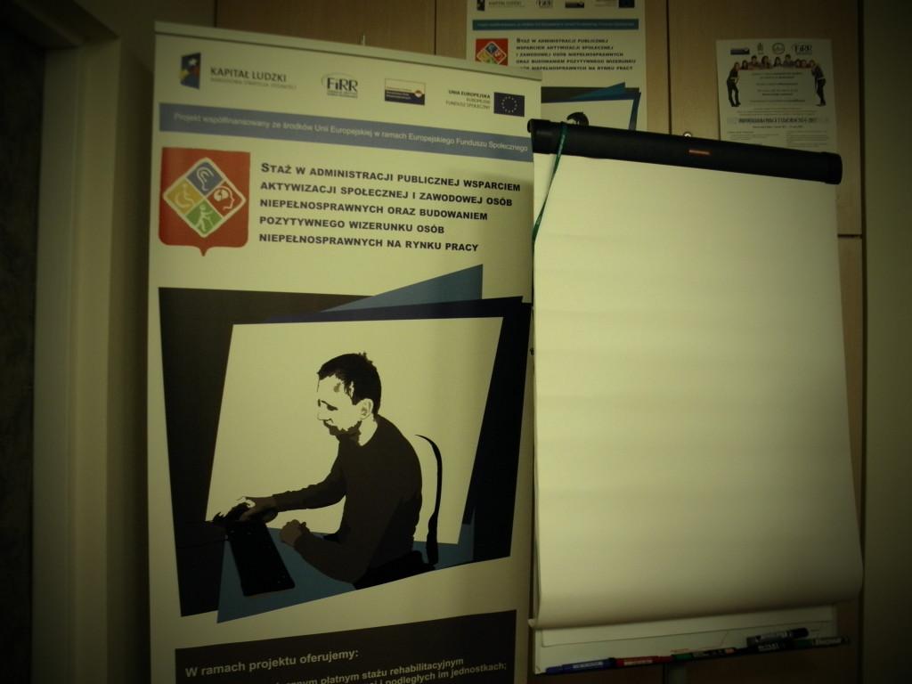 Zdjęcie: Plakat reklamujący projekt stażowy, a obok flipchart z czystymi kartkami w salce szkoleniowej