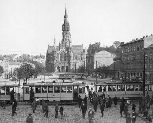 Zdjęcie czarno-białe, stara fotografia przedstawiająca Kraków w dawnych latacg. Na pierwszym planie trawmaj i ludzie, w tle kościoł